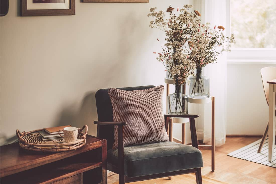 Contemporary Chair As A Companion Piece To A Side Table, armchair with throw pillow, flower arrangement