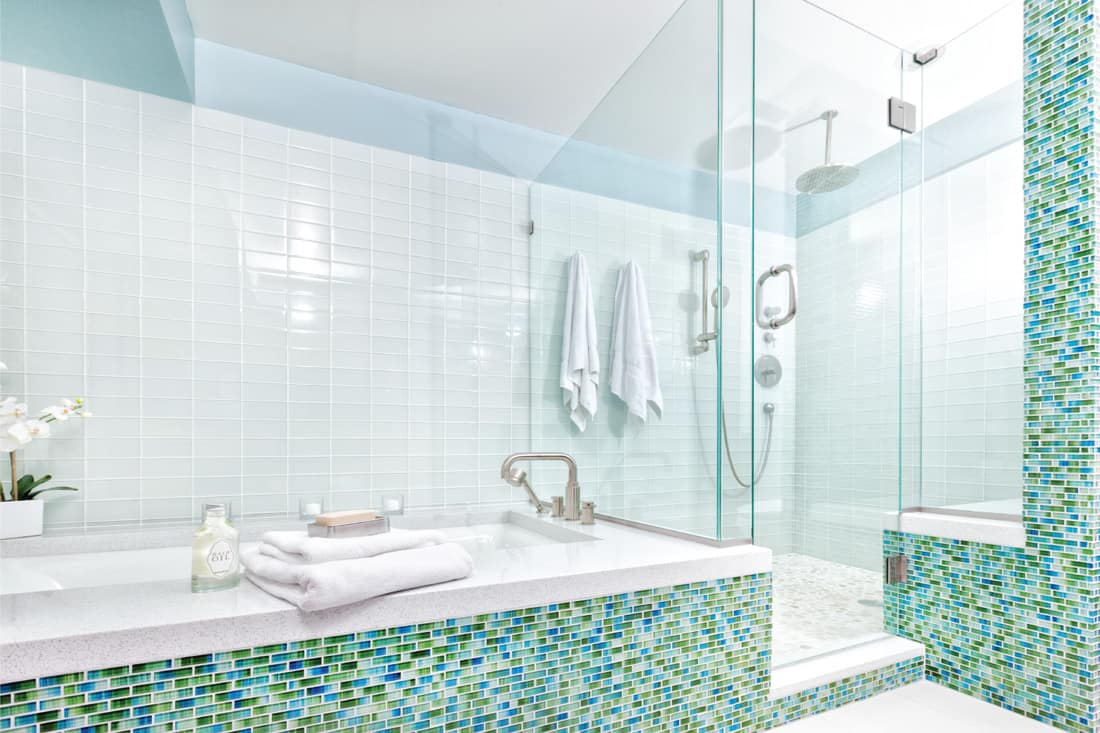 Contemporary residential home bathroom modern design featuring glass shower stall, bathtub, and glass wall tiles