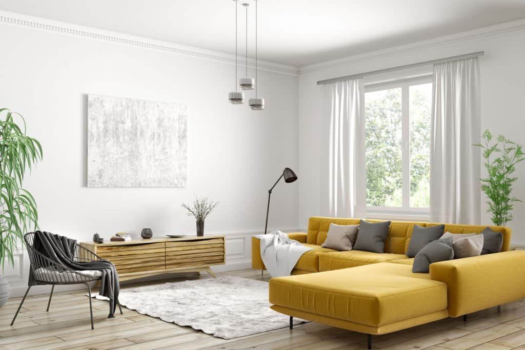 Contemporary living room with a long yellow sectional sofa with gray throw pillows, indoor plants, and silver dangling lamp
