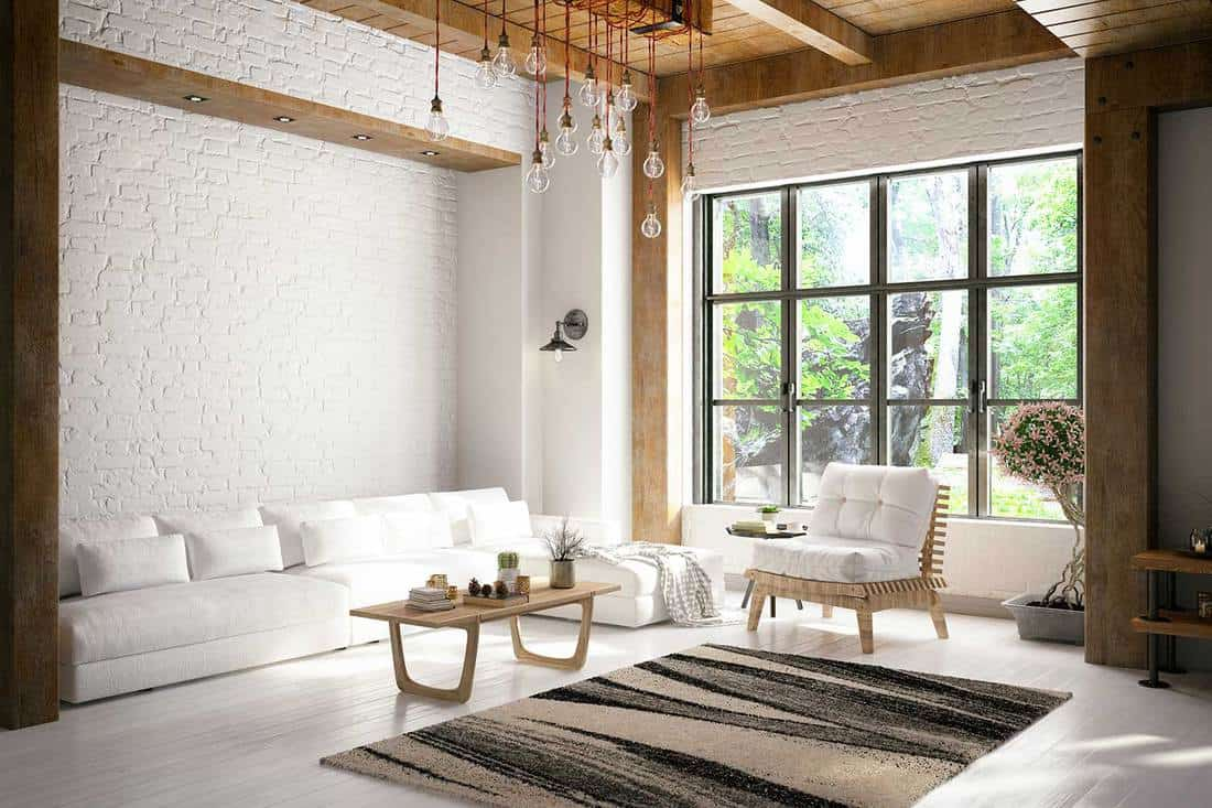 Cozy design loft room with white corner sofa and brick wall