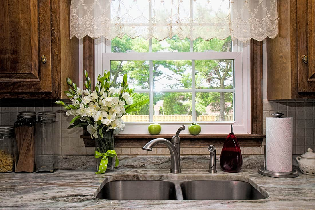 Cozy kitchen window and sink view with sheer valance over windo