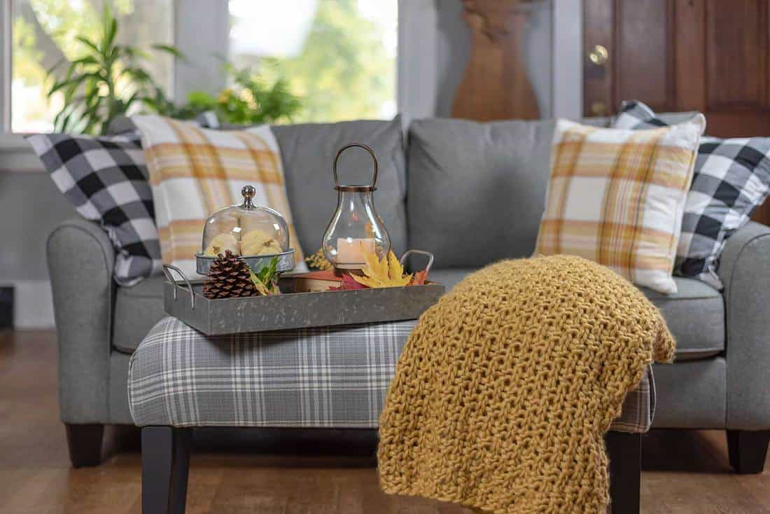 Cozy living room decorated for fall with gray sofa and throw pillows