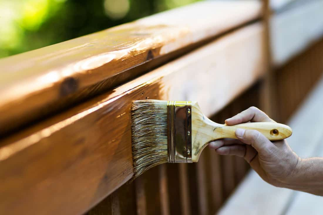 Cropped view of male carpenter applying stain to wooden furniture