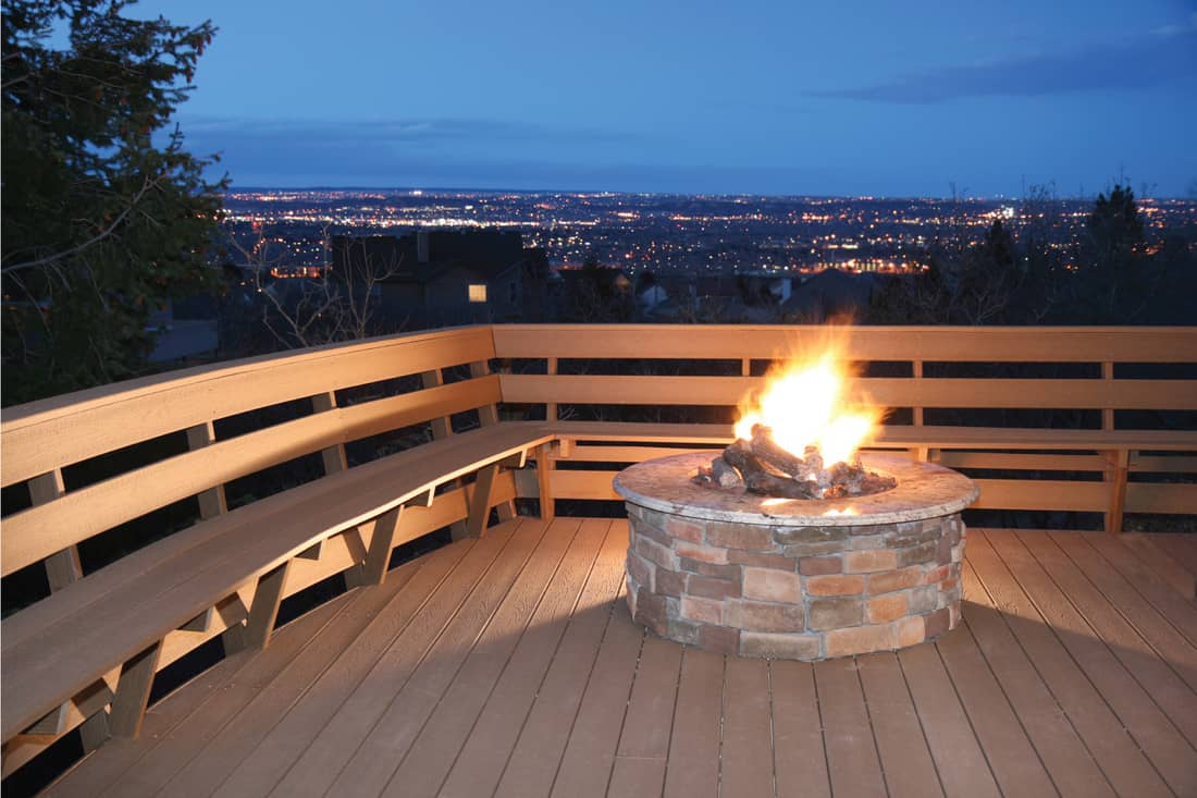 Deck with Built-In Seating and fire pit overlooking city lights at dusk.