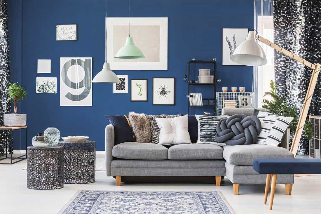 Designer metal tables near gray corner couch in spacious living room with gallery on blue wall