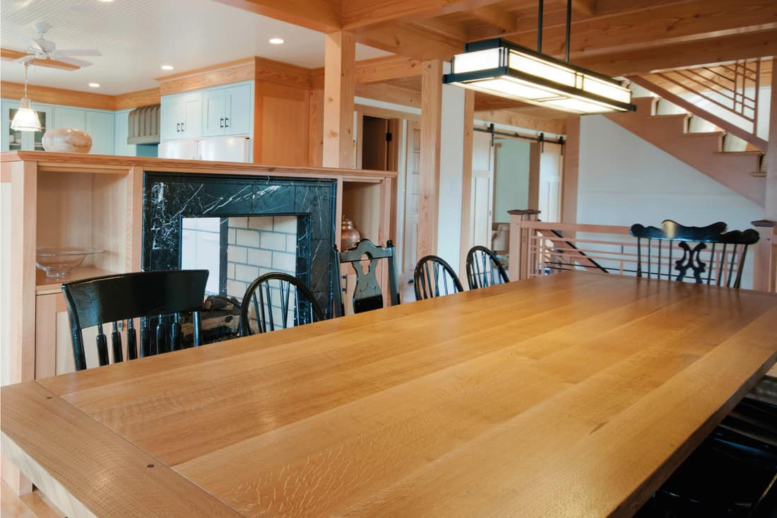 Dining room table in a post and beam home interior with a Prairie School lamp and black chairs