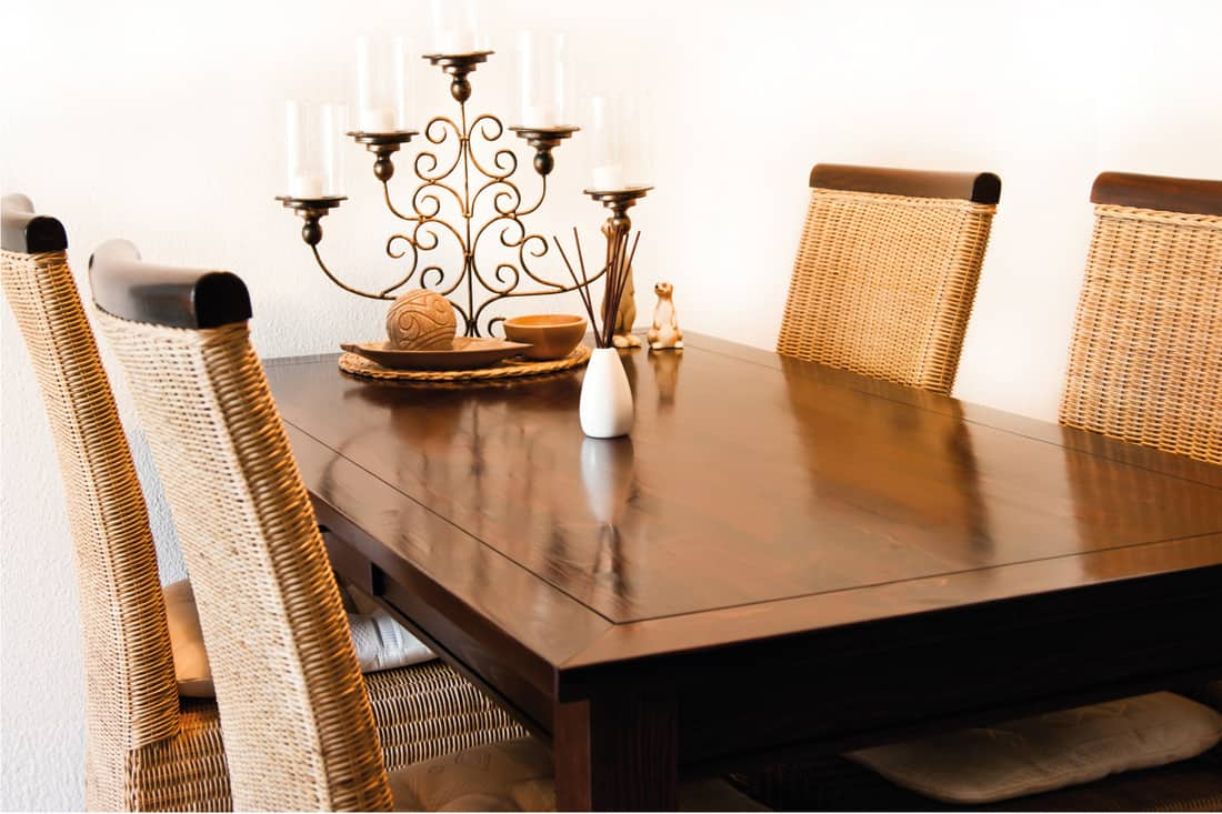 Dining table in lighter natural wood tones with rattan chairs and decoration