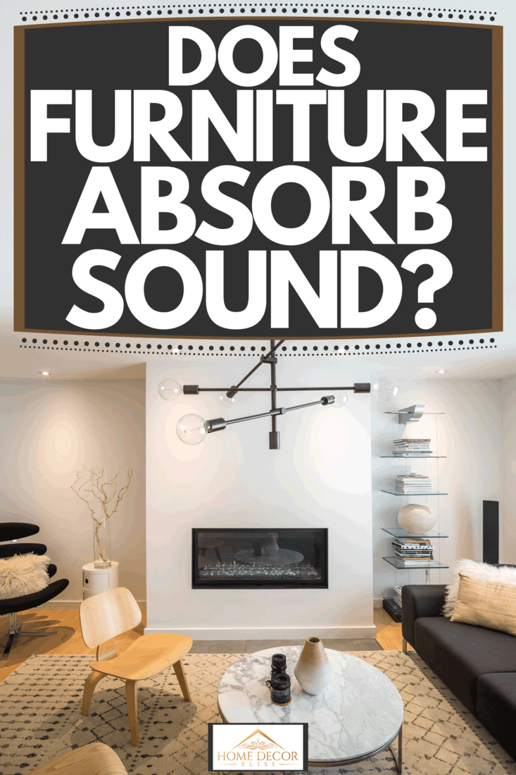 A luxurious and stylish living room with an abstract chandelier design, long black sofa, and a round ceramic table, Does Furniture Absorb Sound?