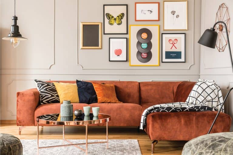 Eclectic living room interior with comfortable velvet corner sofa with pillows, assorted picture frames on the wall. Should Picture Frames All Be The Same Color