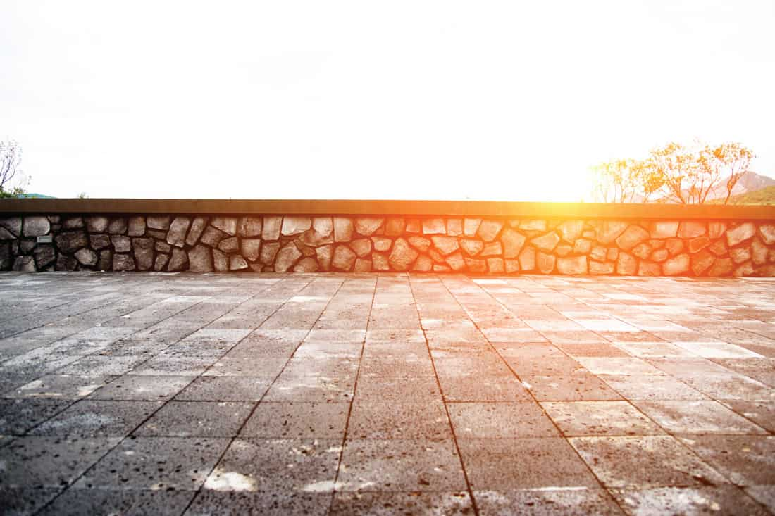 Empty cement platform with stone wall against sky background