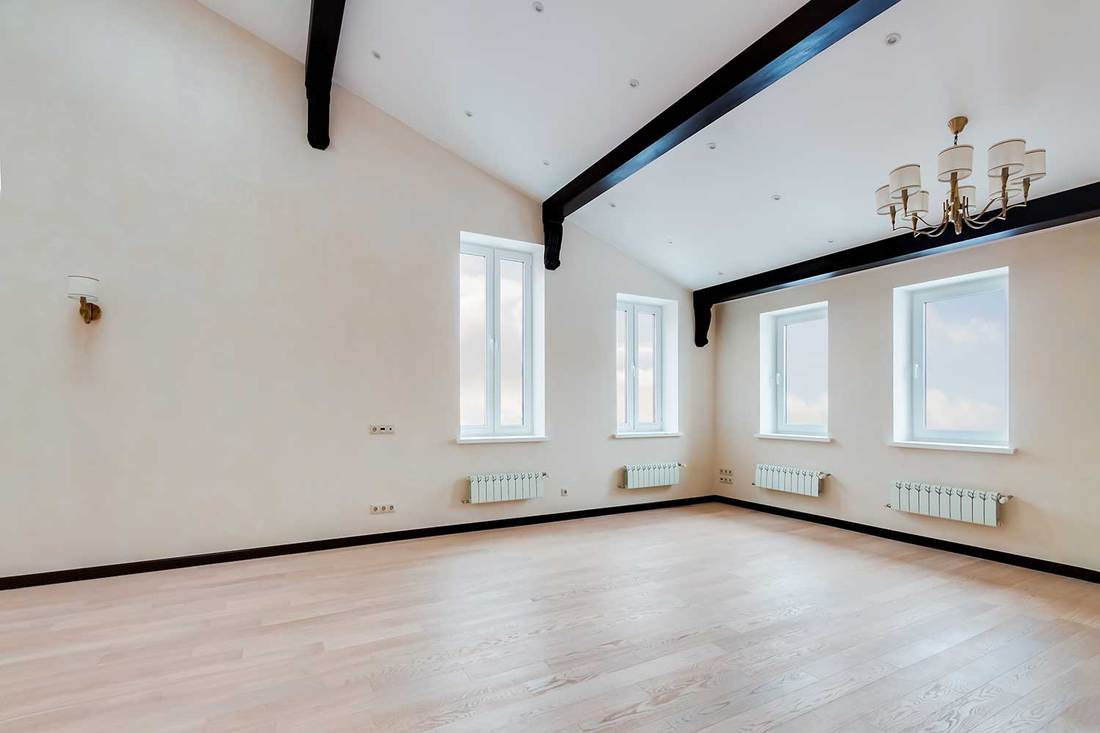 Empty light room with wide white window and chandelier and wooden black beams on the ceiling