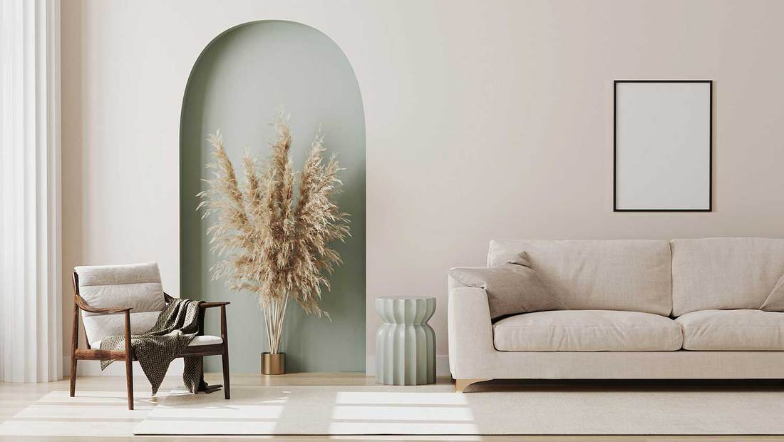 Empty poster frame on beige wall in living room interior with modern furniture and decorative green arch with trendy dried flowers, white sofa and armchair