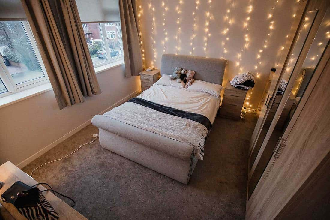 Empty student bedroom decorated with twinkle lights and teddy bears