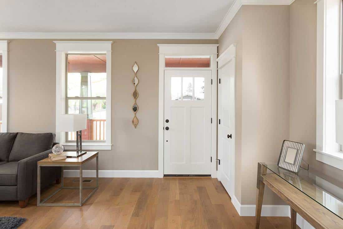 Entryway with hardwood floors, couch, lamp and several windows