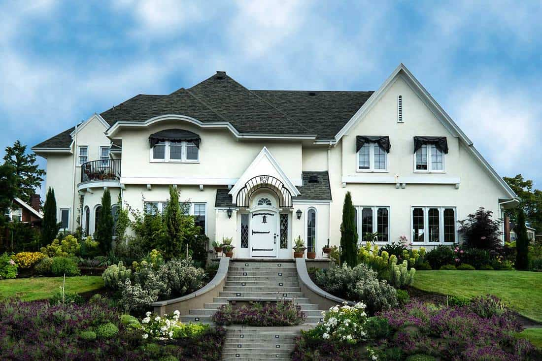 Exterior of white stucco luxury house with landscaped yard