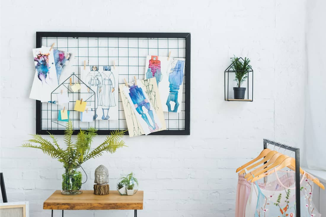 Fashion sketches on board with frame near sticky notes and plants with green leaves