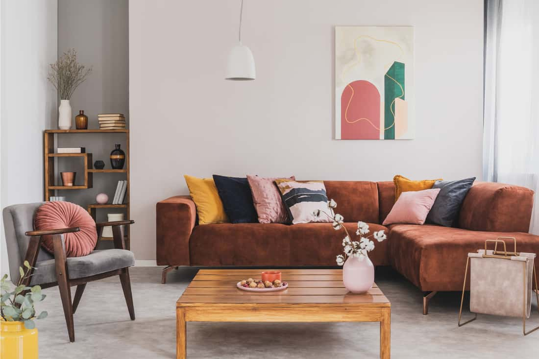 Flowers in vase on wooden coffee table in fashionable living room interior with brown corner sofa with pillows and gray chair