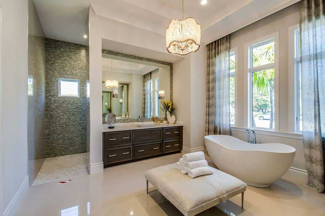 Freestanding tub and ottoman stool in center of bathroom with shower in the background