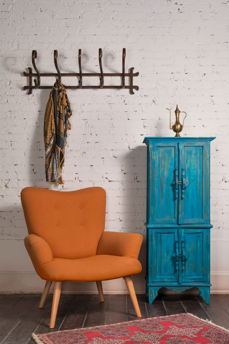 French orange wingback armchair with wooden legs, vintage blue cupboard, and wall hanger with ornate scarf on white bricks wall and grunge wooden parquet with red decorated carpet