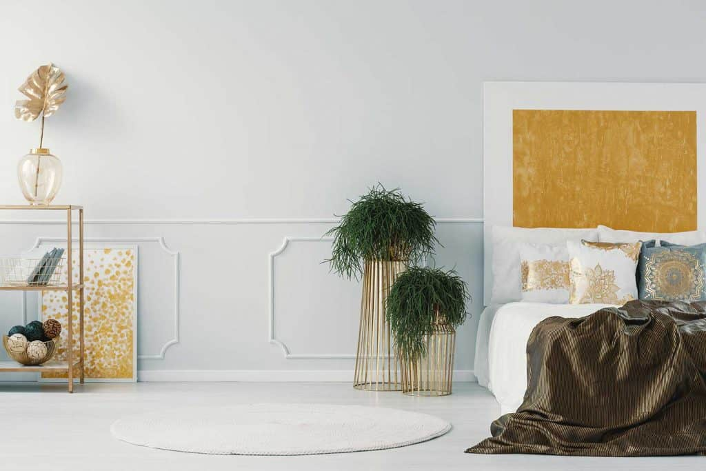 Glamor bedroom interior with plants in golden pots, bed and wall molding