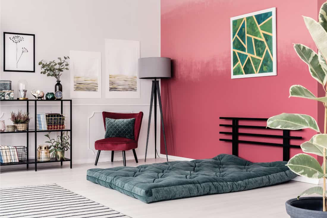Green and yellow poster with geometric pattern hanging on burgundy wall in bright room with mattress on the floor