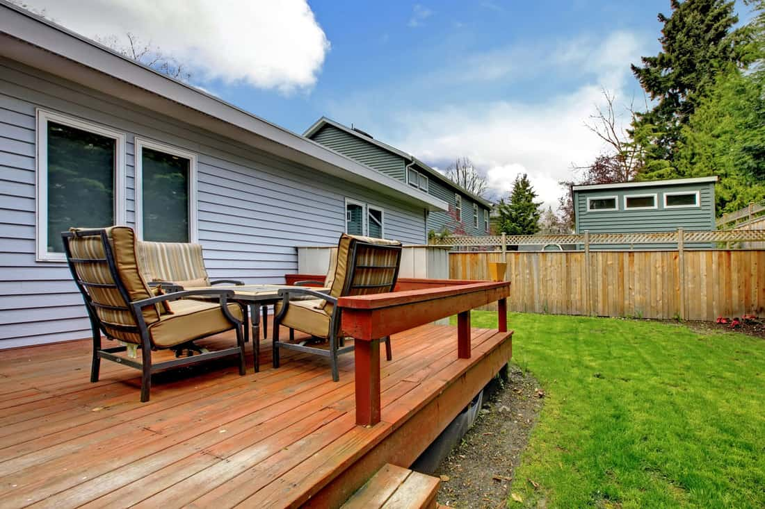 Grey small house with simple deck and outdoor chairs