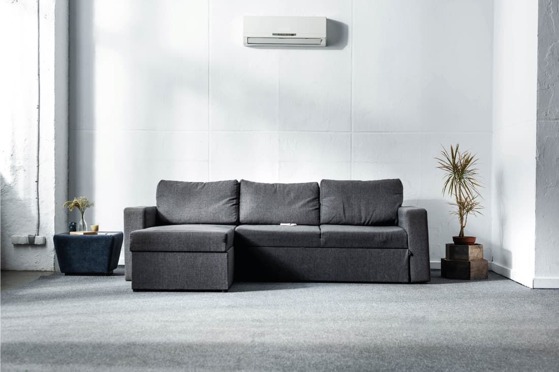 Grey sofa near green plants in modern living room. Mix Up Your Greys For Monochromatic Differences