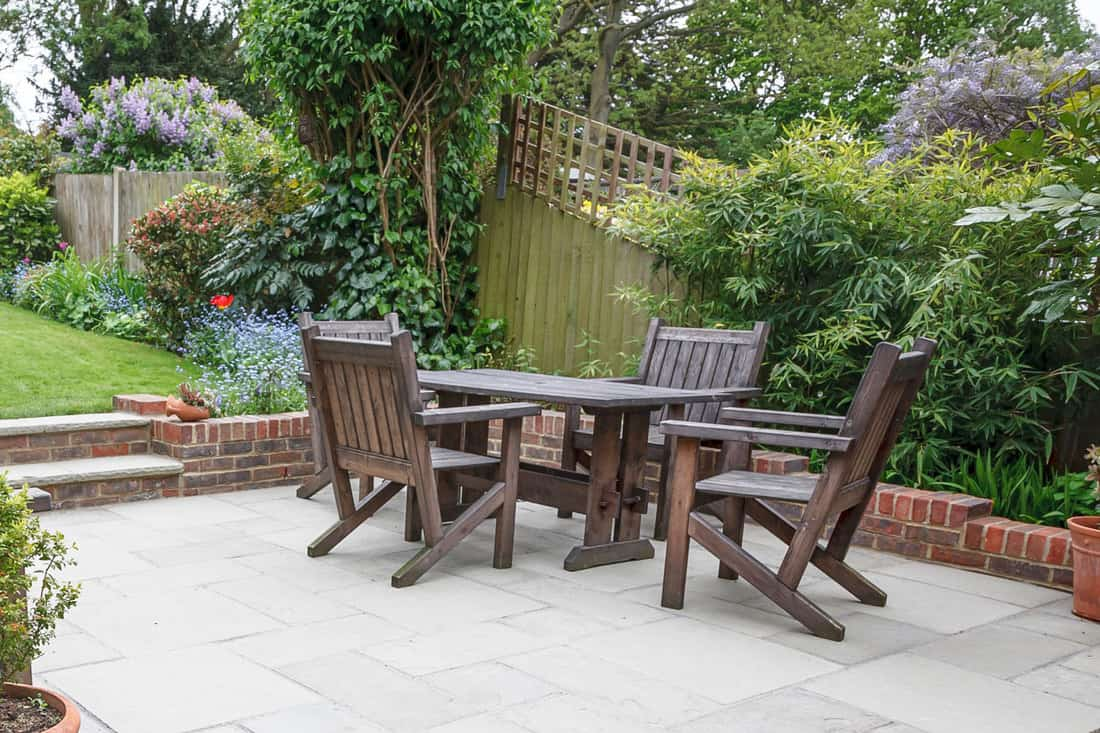 Hard landscaping, new luxury stone patio and garden with wood furniture for outdoors