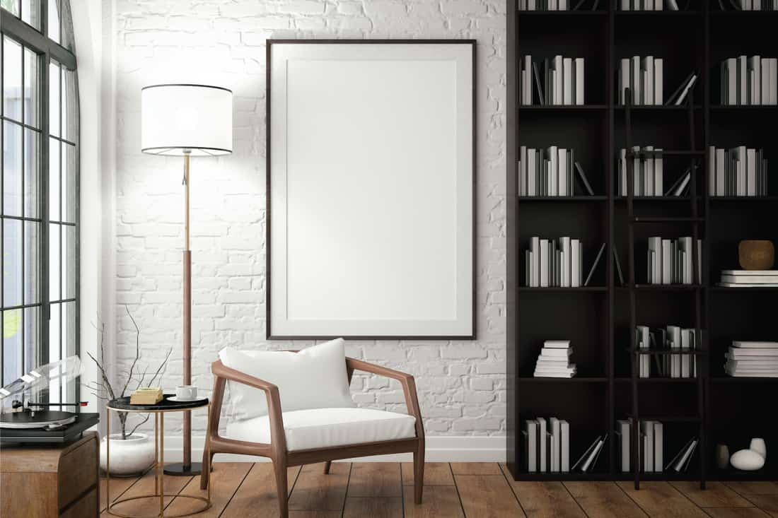 High Arm, Wooden Frame Chair in a white room with open bookshelves and floor lamp