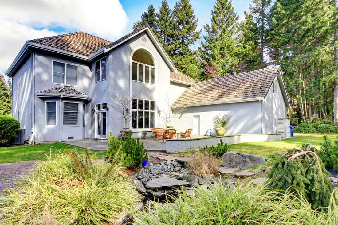 Home exterior of large grey classic house with pine trees