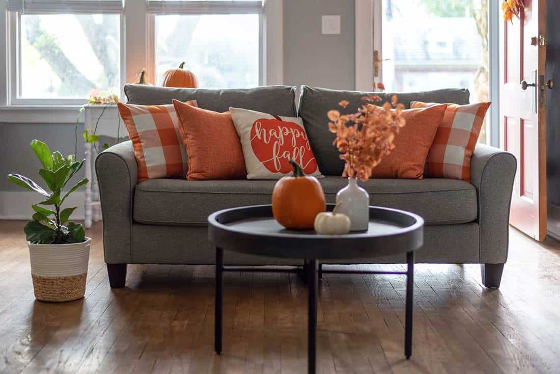 Home interior decorated for fall with orange accent pillows on the sofa