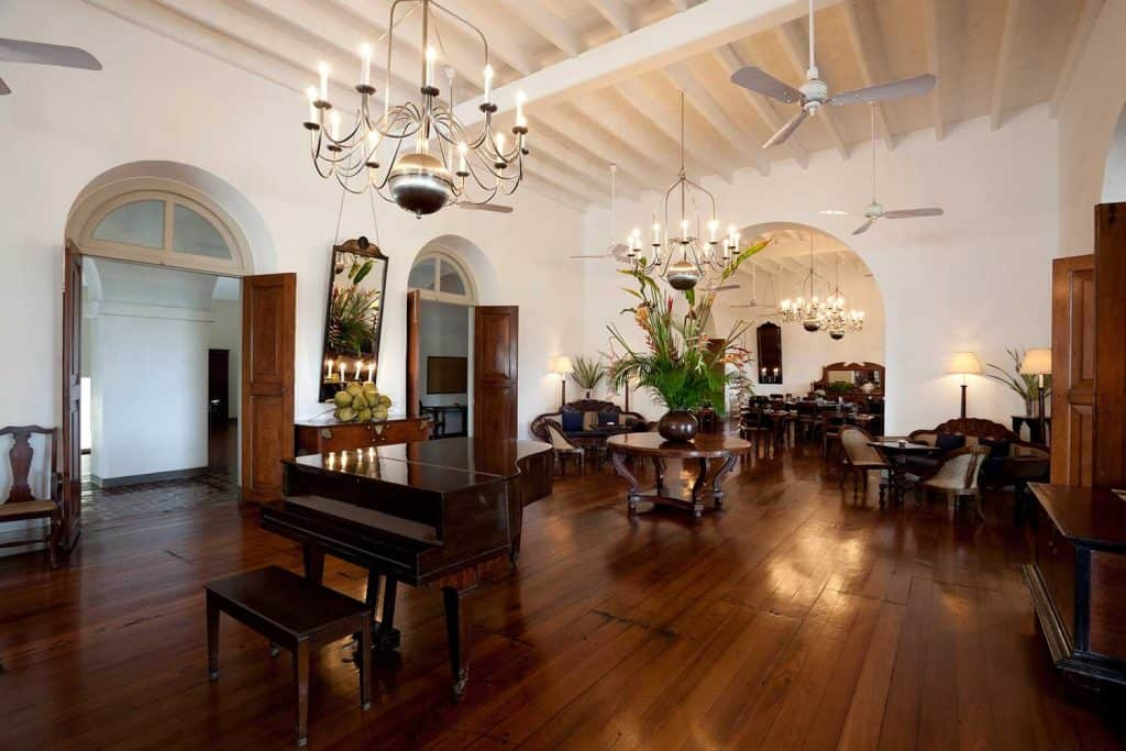 Hotel lobby with wooden furniture, chandeliers and ceiling fans