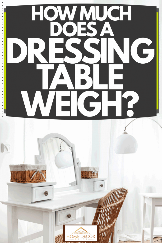 A white dresser table with small basket containers, a white framed glass mirror, and a wicker chair inside a white bedroom, How Much Does A Dressing Table Weigh?