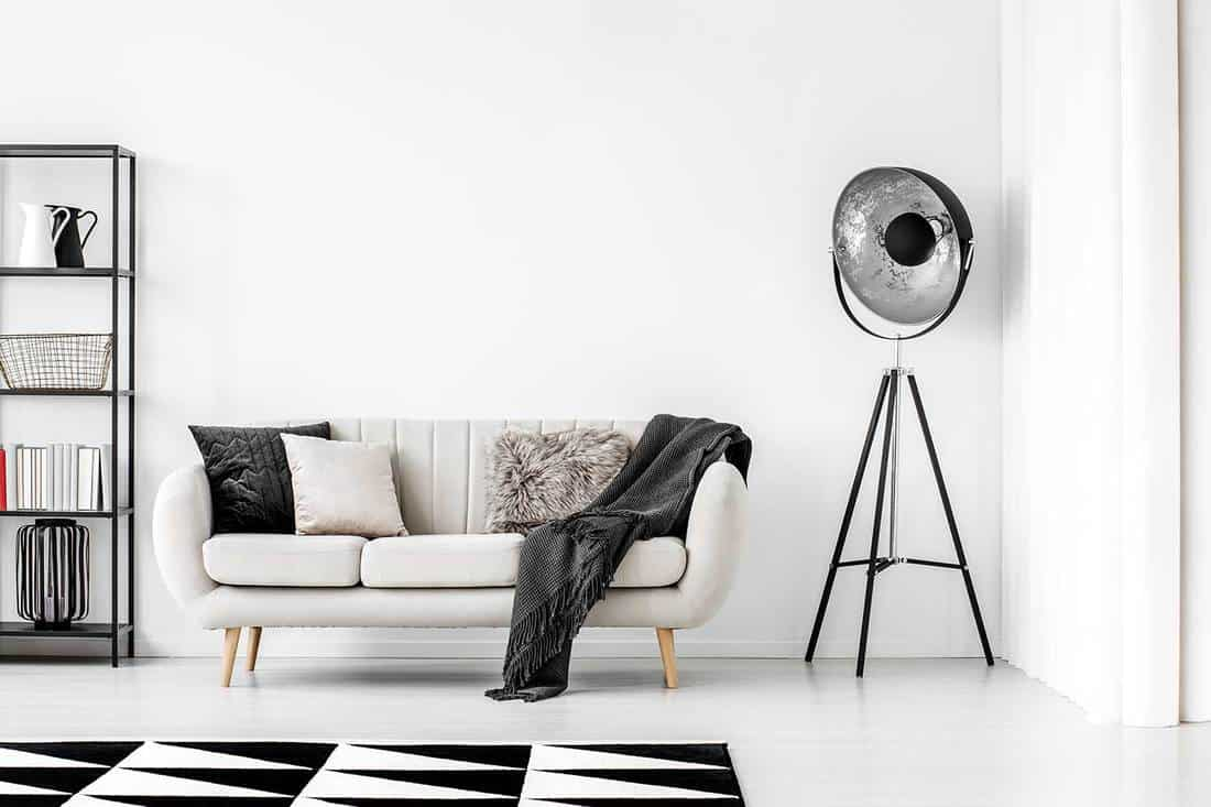 Industrial black lamp next to beige couch with blanket and pillows