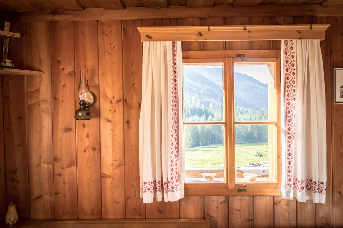 Inside of a rustic wooden hut or cabin with small window