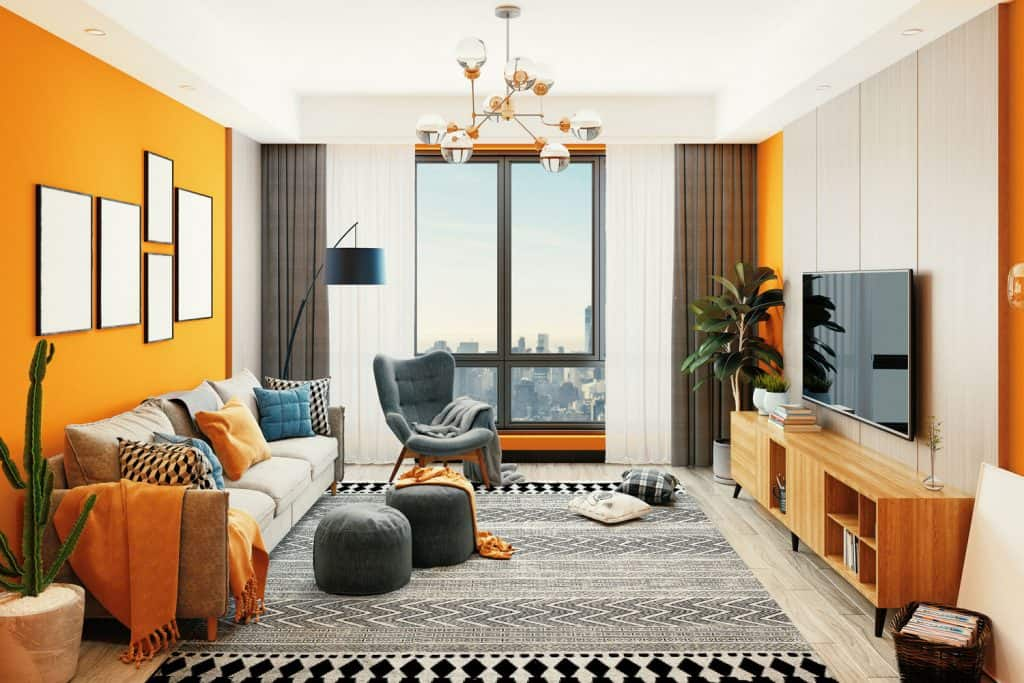 Interior of a luxurious modern contemporary living room with bright orange colored walls, drapes, and throw pillows