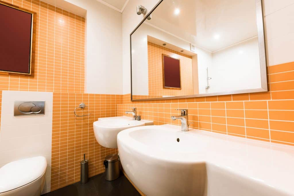 Interior of a modern bathroom with orange tiled walls, white urinals and lavatory, and a huge mirror hanged on the wall