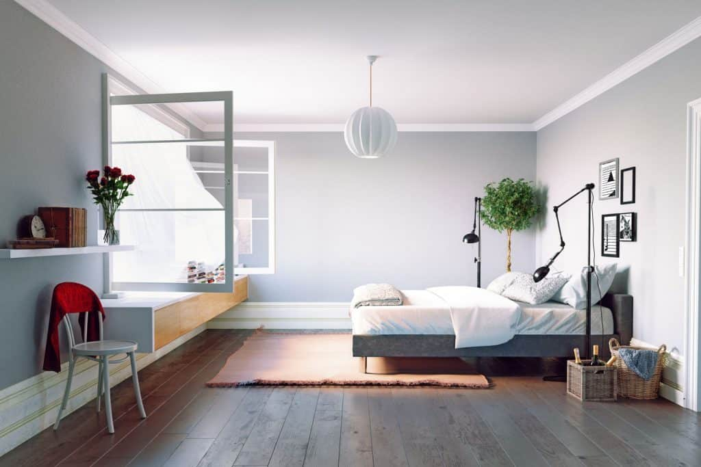 Interiora of a modern bedroom with white painted walls, minimalist themed design huge picture window, and hardwood flooring