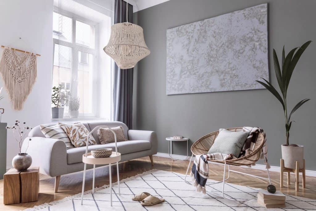 Interior of a modern boho inspired living room with Rattan chairs, small round coffee tables, and an abstract wall painting