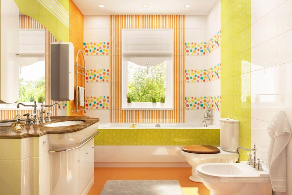 Interior of a orange colored bathroom with an white tiled walls, orange flooring, and decorative tiles on the bathtub window
