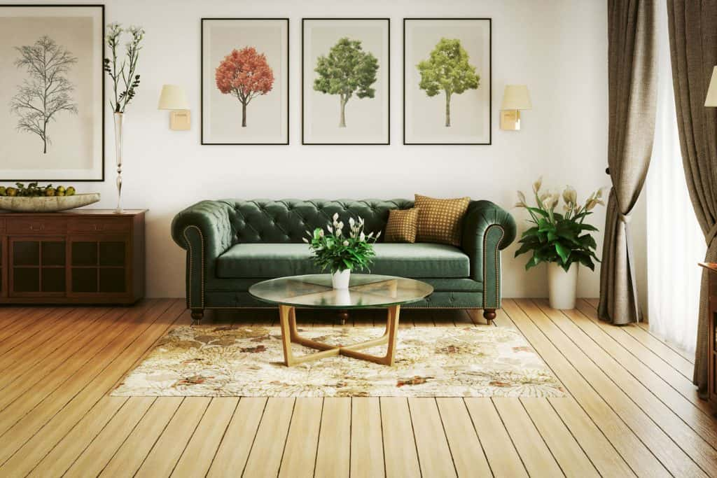 Interior of a rustic inspired living room with wooden panel flooring, glass coffee table with an area rug underneath, and a green natuzzi sofa with paintings on the wall