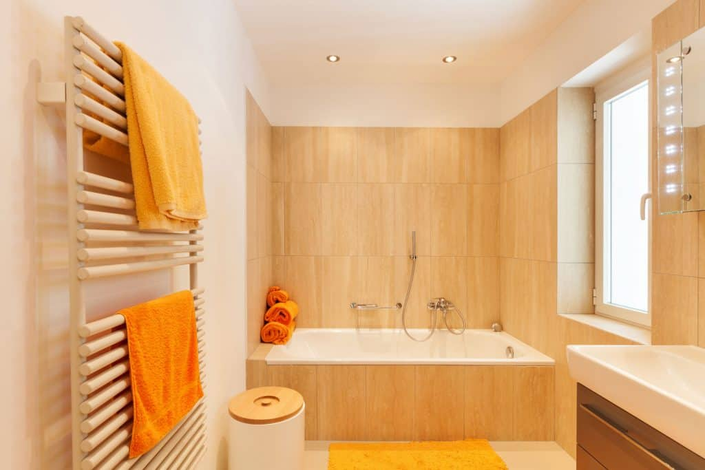 Interior of a rustic themed bathroom with a wooden pattern orange tiles and a wooden shower rack with orange towels