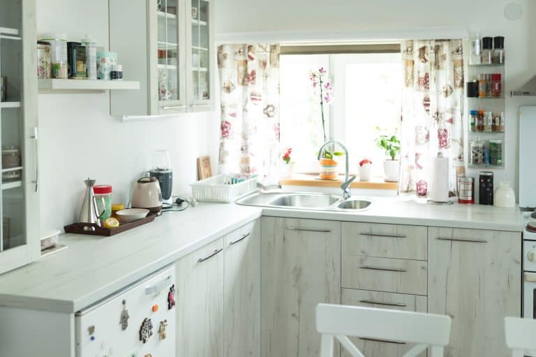 Interior of a small white themed kitchen with floral blinds on the window and indoor plants on the windowsill, What Are The Best Blinds For A Kitchen Window?