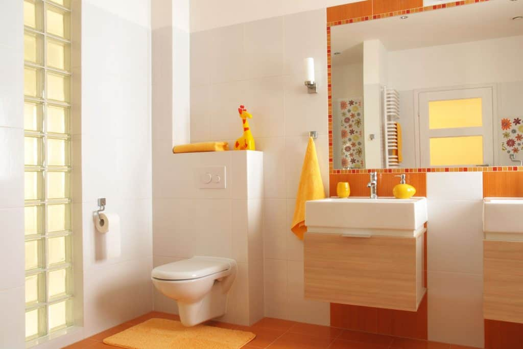Interior of a white walled bathroom with an orange wall vanity area
