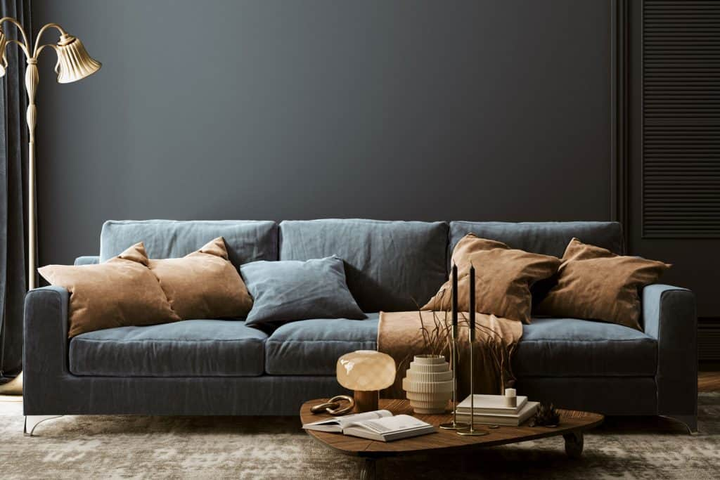 Interior of a elegant dark and warm themed living room with an dark blue sofa with blue and brown throw pillows