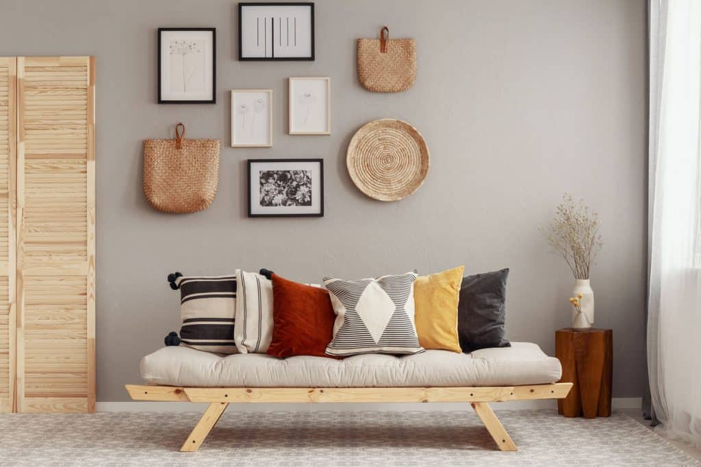 Interior of an elegant living room with picture frames on the wall, a small armless sofa, and different throw pillow on the sofa