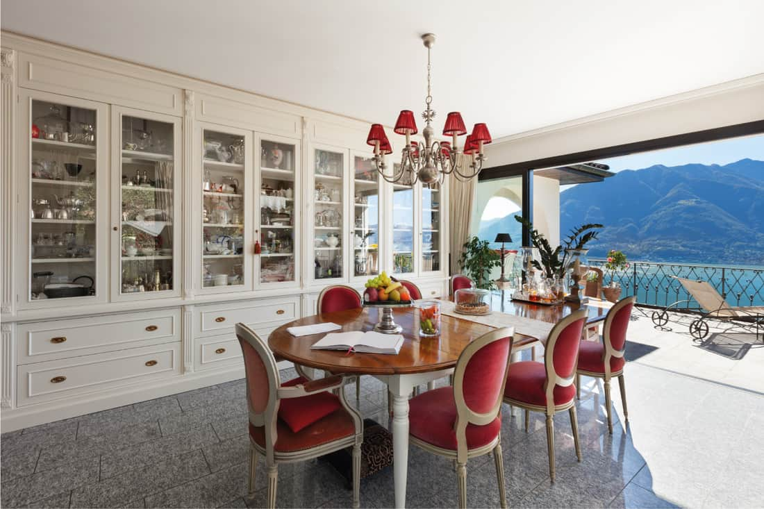 Interior of house, table and chairs of a dining room, classic decor, oak table with red chairs