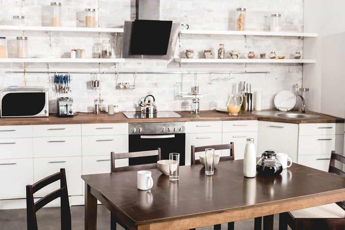 Interior of modern white kitchen with table ready for breakfast