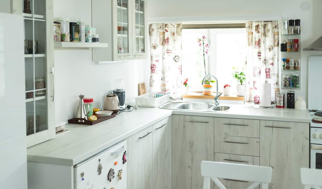 Interior of modern white wooden kitchen with small window and curtain