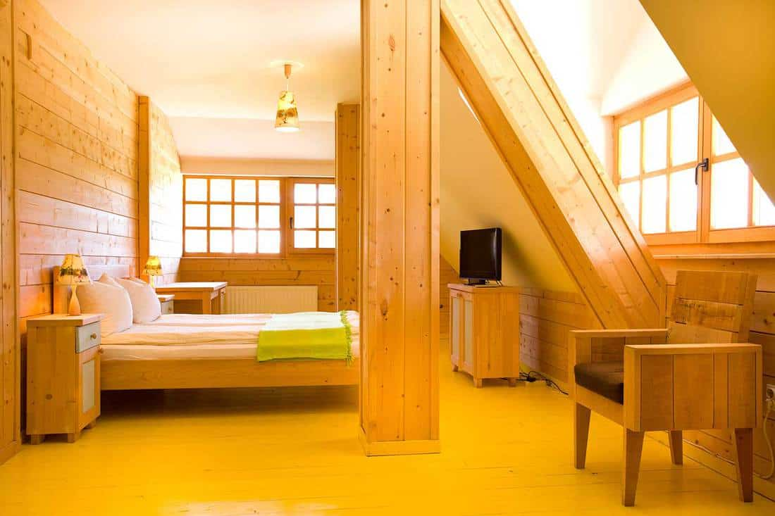 Interior of wooden cottage bedroom on the attic